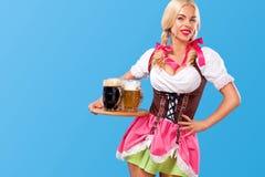 Junges sexy Oktoberfest-Mädchen - Kellnerin, ein traditionelles bayerisches Kleid tragend, dienende große Bierkrüge auf blauem Hi lizenzfreie stockbilder