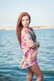 Junges sexy rotes Haarmädchen in der mehrfarbigen Bluse, die auf dem Strand aufwirft Sinnliche attraktive Frau mit dem langen Haa Lizenzfreie Stockfotografie