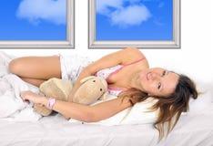 Junges schönes Mädchen im Nachthemd, das auf Bett im Schlafzimmer umarmt das Teddybärlächeln glücklich liegt Stockbild