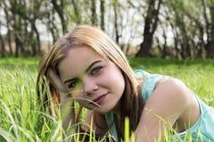 Junges sinnliches lächelndes blondes Lügen auf dem Gras im Sonnenlicht Lizenzfreies Stockfoto