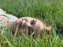 Junges sinnliches lächelndes blondes Lügen auf dem Gras im Sonnenlicht Stockfotografie