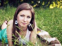 Junges sinnliches lächelndes blondes Lügen auf dem Gras im Sonnenlicht Lizenzfreie Stockfotos