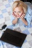 Junges smilingwoman Lügen auf Fußboden mit einem Laptop Lizenzfreie Stockfotografie