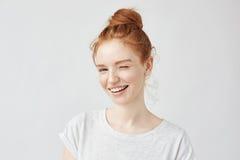 Junges spielerisches schönes Mädchen mit dem lächelnden Blinzeln des foxy Haares, Kamera betrachtend Getrennt auf weißem Hintergr Stockfotos
