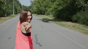 Junges sportives Mädchenlachen Attraktive kaukasische Frau, die zur Kamera schaut Brunette Mädchen im rosa Hemd lädt ein, um ihr  stock video