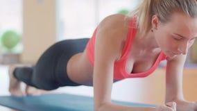 Junges Sportlerinmädchen der dünnen Eignung, das Plankenübung mit Beinkonzepttrainingstraining crossfit Gymnastikkreuz tut stock video footage