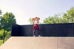 Junges sportliches Frauenholdingskateboard hinter Kopf stockbild