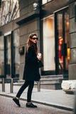 Junges stilvolles Mädchen, überschreiten durch Windows Tragende moderne Gläser und ein schwarzer Mantel Hält Kaffee Abstraktes Sc Lizenzfreie Stockfotos
