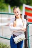 Junges stilvolles Mädchen in der weißen Bluse und in den Blue Jeans Lizenzfreies Stockfoto
