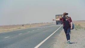 Junges stilvolles Mädchen im Cowboy kleidet das Handeln des Per Anhalter fahrens in der Wüste, auf der Straße Sie trägt Rucksack