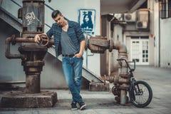 Junges stilvolles Mannmodell nahe dem Dachbodenmetallrohr und -fahrrad Stockbild