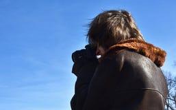 Junges Straßenphotographschießen mit DSLR-Kamera, blauer Himmel, Hintergrundbeleuchtung, sonniger Tag stockfoto