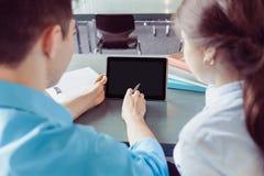 Junges Student Lernen und Hände, die auf Tablette in der Bibliothek schreiben Lizenzfreies Stockfoto