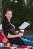 Junges Studentenmädchen, das ein Buch im Park liest Stockfoto