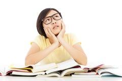 Junges Studentenmädchen, das mit Buch auf dem Schreibtisch denkt stockfoto