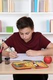 Junges Studentenschreiben in seinem Übungsbuch in der Schule Lizenzfreie Stockbilder
