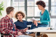 Junges Studentenschreiben während des Brainstorming für eine Gruppenaufgabe stockfoto