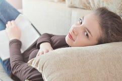 Junges Studentinlesebuch, das sich zu Hause entspannt Lizenzfreie Stockfotos