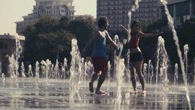 Junges Tanzen des glücklichen Paars im Brunnen