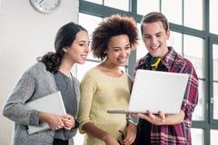 Junges Team, das über einer Geschäftsdarstellung auf Laptop schaut Stockbilder