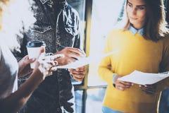 Junges Team von den Mitarbeitern, die große Diskussion im sonnigen Büro nahe dem Fenster machen Bemannen Sie das Halten eines Pap Lizenzfreie Stockbilder