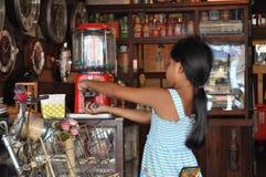 Junges thailändisches Mädchen erhält Süßigkeit von einer alten Maschine in einem Weinlesegeschäft lizenzfreies stockbild