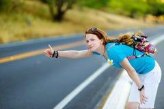 Junges touristisches Per Anhalter fahren entlang einer Straße Lizenzfreies Stockbild