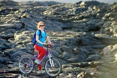 Junges touristisches Radfahren auf Lavafeld auf Hawaii Weiblicher Wanderer, der zum Lavasendegebiet an Kalapana-Stadt auf ihrem F lizenzfreie stockbilder