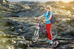 Junges touristisches Radfahren auf Lavafeld auf Hawaii Weiblicher Wanderer, der zum Lavasendegebiet bei Kalapana auf ihrem Fahrra lizenzfreies stockfoto