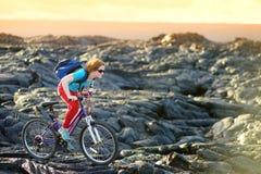 Junges touristisches Radfahren auf Lavafeld auf Hawaii Weiblicher Wanderer, der zum Lavasendegebiet bei Kalapana auf ihrem Fahrra stockfotografie