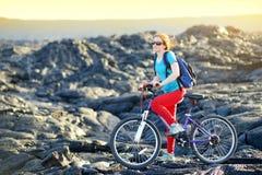 Junges touristisches Radfahren auf Lavafeld auf Hawaii Weiblicher Wanderer, der zum Lavasendegebiet bei Kalapana auf ihrem Fahrra stockfotos