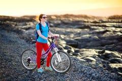 Junges touristisches Radfahren auf Lavafeld auf Hawaii Weiblicher Wanderer, der zum Lavasendegebiet bei Kalapana auf ihrem Fahrra stockbild