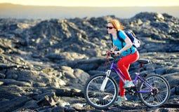 Junges touristisches Radfahren auf Lavafeld auf Hawaii Weiblicher Wanderer, der zum Lavasendegebiet bei Kalapana auf ihrem Fahrra stockfoto