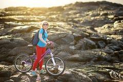 Junges touristisches Radfahren auf Lavafeld auf Hawaii Weiblicher Wanderer, der zum Lavasendegebiet bei Kalapana auf ihrem Fahrra lizenzfreie stockfotos