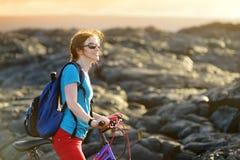 Junges touristisches Radfahren auf Lavafeld auf Hawaii Weiblicher Wanderer, der zum Lavasendegebiet bei Kalapana auf ihrem Fahrra lizenzfreie stockfotografie