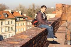 Junges touristisches Sitzen auf der Wand Stockfotografie