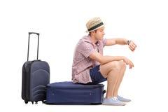 Junges touristisches Sitzen auf seinen Taschen und zu der Zeit schauen Stockbild