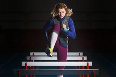 Junges Training des weiblichen Athleten, das mit Hürden läuft stockfoto