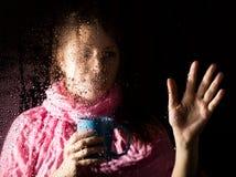 Junges trauriges Frauenporträt hinter dem Fenster im Regen mit Regen fällt auf es Mädchen, das ein Cup des heißen Getränks anhält Stockfotos
