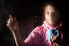 Junges trauriges Frauenporträt hinter dem Fenster im Regen mit Regen fällt auf es Mädchen, das ein Cup des heißen Getränks anhält Stockfoto