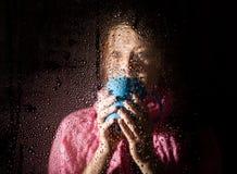 Junges trauriges Frauenporträt hinter dem Fenster im Regen mit Regen fällt auf es Mädchen, das ein Cup des heißen Getränks anhält Stockbilder