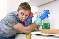 Junges trauriges frustriertes Mannreinigungs- und -reinigungshauptspülbecken Stockfoto