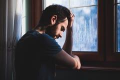 Junges trauriges wütendes am Fenster sitzen lizenzfreies stockfoto