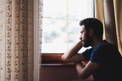 Junges trauriges wütendes am Fenster sitzen Stockbilder