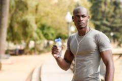 Junges Trinkwasser des schwarzen Mannes bevor dem Laufen in städtisches backgroun stockfotos