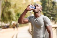 Junges Trinkwasser des schwarzen Mannes bevor dem Laufen in städtisches backgroun stockbild