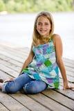 Junges Tween, das auf einem Pier sitzt Lizenzfreies Stockbild
