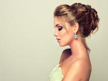 Junges und attraktives blondes Modell kleidete in den Abendkleid- und -schmuck earings an Lizenzfreie Stockfotos