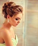 Junges und attraktives blondes Modell kleidete in den Abendkleid- und -schmuck earings an Stockbild