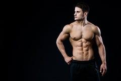 Junges und geeignetes männliches Modell, das seine Muskeln schauen nach links lokalisiert auf schwarzem Hintergrund mit copyspace Stockfotografie